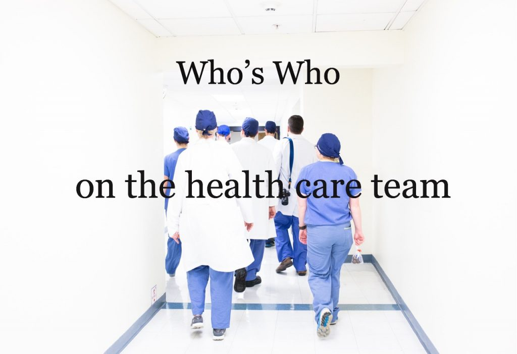 group of people in scrubs walking hospital hall together