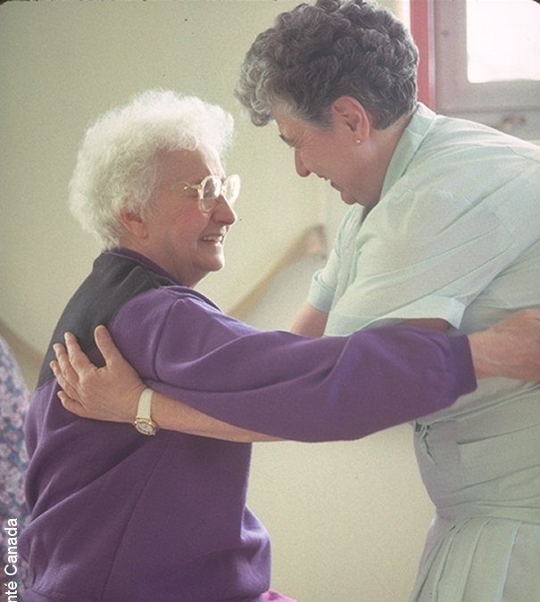 caregiver assisting an older woman to stand