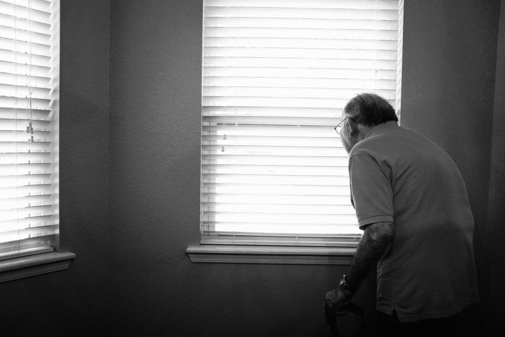 black & white photo older man alone looking out a window